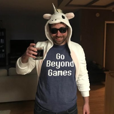 Mark in a unicorn onesie raising a glass of rye and coke.