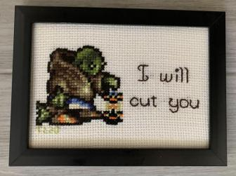 """Tania's cross stitch of Tonberry. It shows Tonberry holding its lantern and says """"I will cut you"""""""