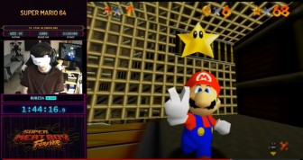 A screenshot of Bubzia's SGDQ run. Bubzia's wearing a kitty blindfold and Mario is giving a peace sign, having just got a star.