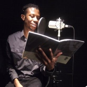 Javon Goard sitting in front of a microphone, reading from an open book