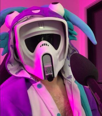 Selfie of LHP64D in Stormtrooper helmet and wearing a Murloc onesie with bare chest showing, sitting in front of a microphone, on stream